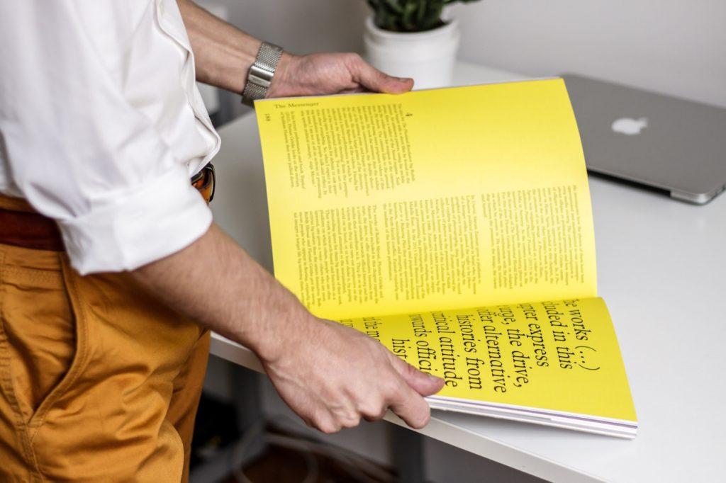 Una persona mostra una rivista aperta